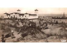 """Palangos paplūdimys su maudyklių pastatais. Iš """"Lietuva senose fotografijose""""."""