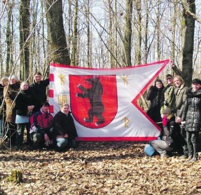 Prie akmens,  į kurį, regis, šaknis įleidęs medis (dešinėje) suplazdėjo Žemaitijos vėliava.