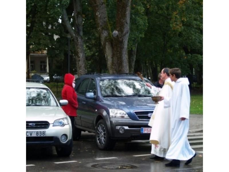Transporto priemones švęstu vandeniu pašlakstė kunigas S.Žilys.